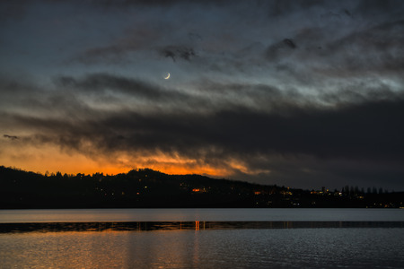 Moon sunset in cloudy sky at evening with Varese lake in the foreground and hills in the background