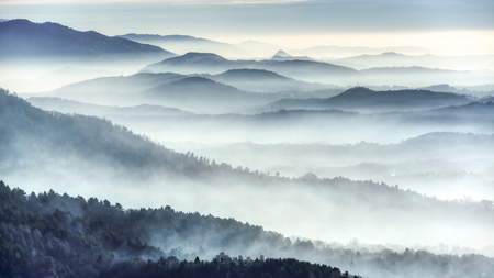 Foggy landscape on the hills in a winter cold morning seen from the mountains near the city of Varese Standard-Bild