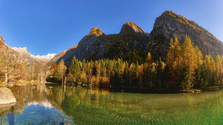 lake at sunset  in autumn season in the mountains of Val di Mello, Italy