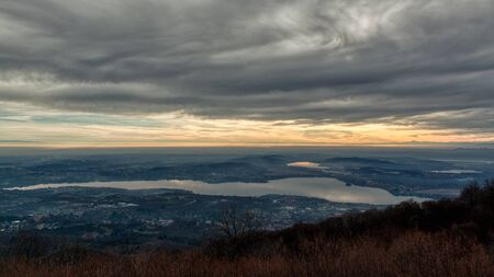 Cloudy sundown over the lake of Varese with mountains at the horizon