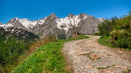 Mountain path with snowy peak in background, Formazza valley in summer season