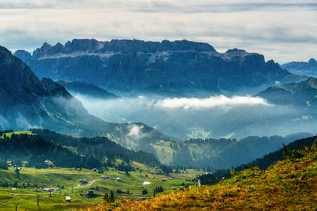 View of Sella Group with fog in the valley, Gardena Valley in summer morning