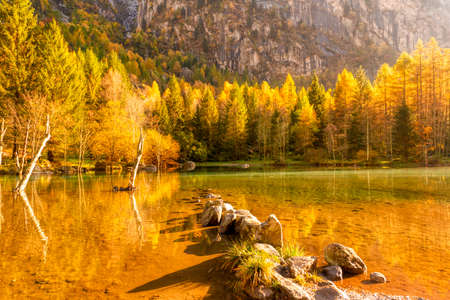bright autumn colors in the Mello valley with reflection on the lake