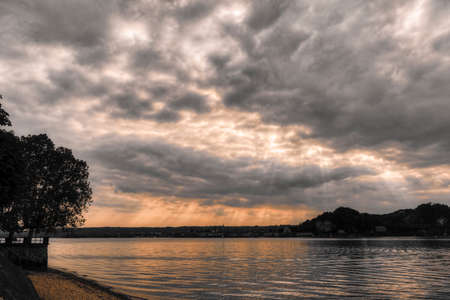 sunbeam over the Major lake at the sunset with cloudy sky in a summer afternoon