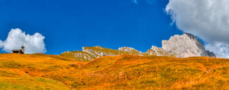 Landscape of natural park of Puez-Odle group in autumn season with little church on the left, Dolomites, South Tyrol, Val Gardena