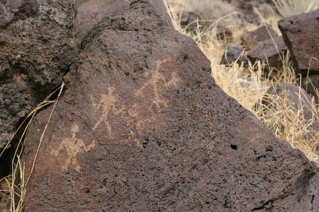 A petroglyph of three people Imagens