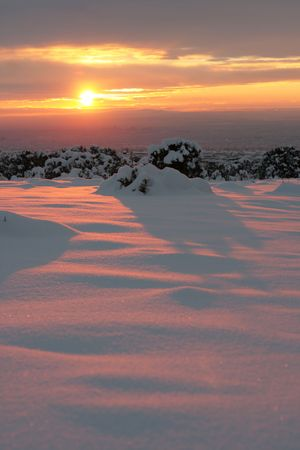 Brilliant sunset casting a pink glow over freshly fallen snow