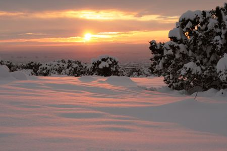 Sun setting with fresh snow on the pinon pines