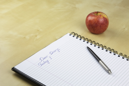 An Unfinished Record in a Diary with an Apple on a Background photo