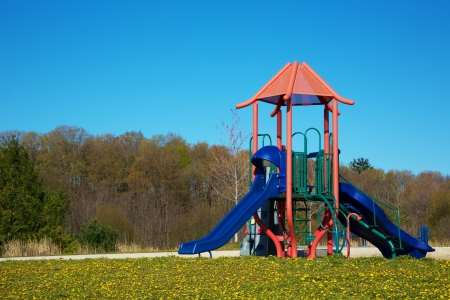A Children Playground with Dandelions and Blue Sky Stock Photo