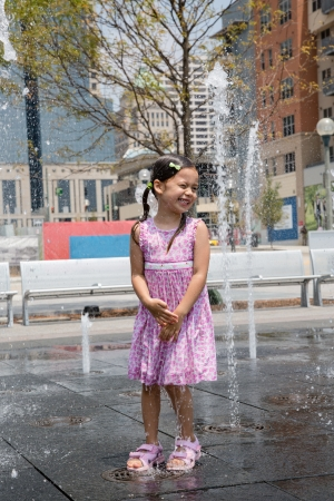 joy pad: Young Girl Having Fun at the Splash Fountain