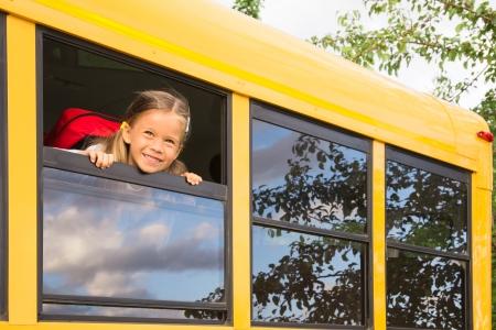 escuelas: Pequeña colegiala mirando a través de una ventana de Schoolbus Foto de archivo