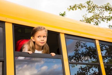 school transportation: Peque�a colegiala mirando a trav�s de una ventana de Schoolbus Foto de archivo
