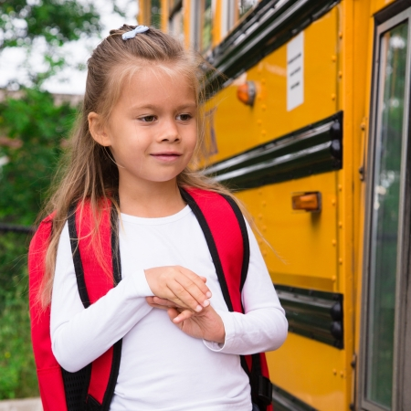 Little Pre-teen Schoolgirl Waiting for Schoolbus to open a Door photo