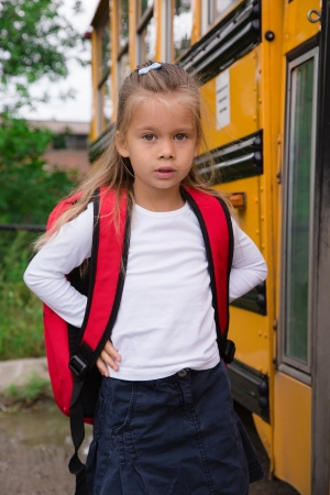 Little Pre-teen Schoolgirl Waiting for Schoolbus to open a Door