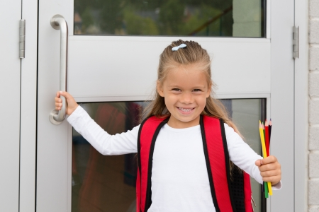 A Little Preteen Schilgirl Holding a Handle of a School Door Showing her Pencils 免版税图像