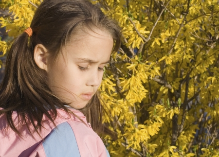 Concerned Little Girl with  Spring Flowers on Background photo