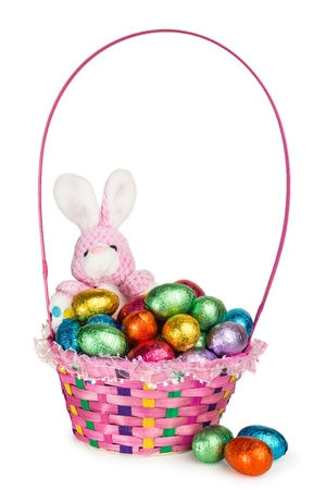 A Toy Bunny and Colorful Basket full of Chocolate Easter Eggs photo
