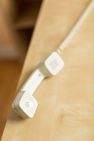 Lone Phone Receiver Laying on an Edge of a Desk Stock Photo - 18344746