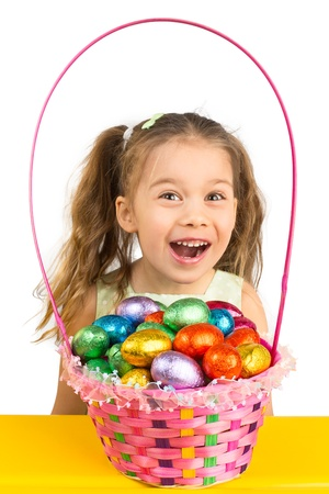 Excited Young Girl and the Basket Full with Chocolate Eggs photo