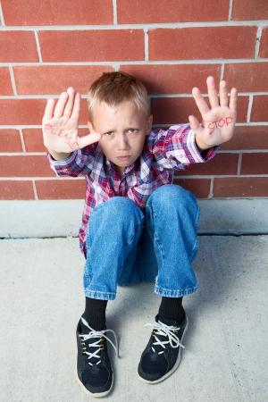 Een pre-teen jongen smeekt om te stoppen met het doen van iets ergs met het schrijven op zijn handpalmen Stockfoto