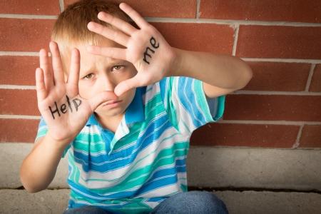 Een pre-teen jongen smeekt om hem te helpen met het bericht geschreven op zijn handpalmen