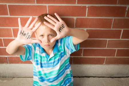 A pre-teen boy is begging to help him showing the message written on his palms photo