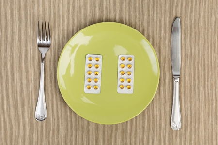 A blister of medications served on a green plate, with fork and knife