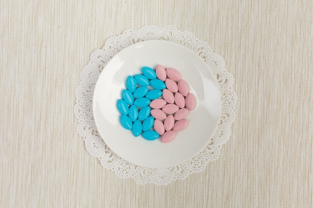 Blue and pink pills on a bone china saucer, arranged in a shape of yin and yang, served on a light grey tablecloth with a fancy naplin Imagens