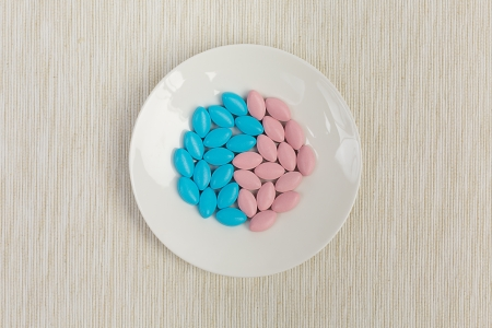 Blue and pink pills on a bone china saucer, arranged in a shape of yin and yang, served on a light grey tablecloth photo