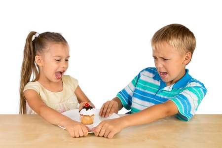 A  girl and a boy are fighting over a single delicious cupcake photo