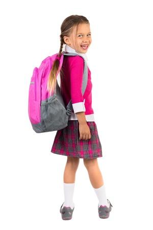 Petite fille en uniforme scolaire rose avec un sac à dos regardant par-dessus l'épaule droite et de rire, isolé Banque d'images - 21419825