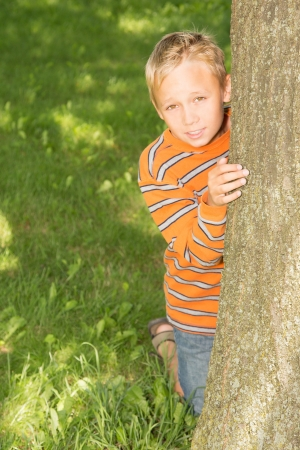 School-age boy is looking from behind a tree in summer park