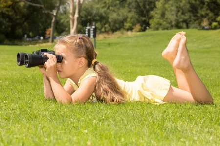 Young girl looking in binoculars while lying on her belly on a green lawn photo