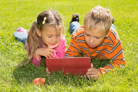 A boy and a girl are looking at the screen of a tablet computer while lying on a green lawn photo