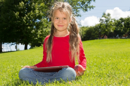 A cute schoolgirl sitting on a green lawn in summer park, holding  tablet computer