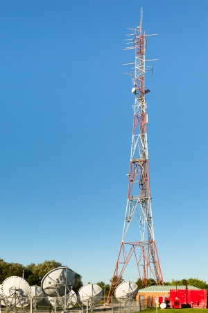 Cell communication tower with telco equipment and sattelite dishes at the bottom