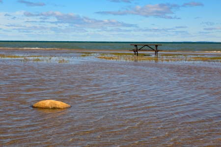 Picnic table on a lake shore with legs slightly flooded by shallow water and yellow stone on a foreground