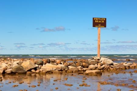 no trespassing: Playa privada, prohibido el paso Se�al en una orilla rocosa