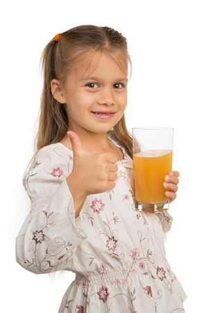 A cute little girl holding a glass with apple juice and showing thumb up