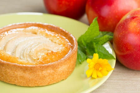 Apple tart on a plate with leaves of mint and a flower of calendula, with red apples on a side