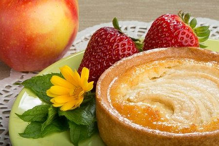 Apple tart with strawberries, mint a flower of calendula on a plate, with an apple on a background Zdjęcie Seryjne