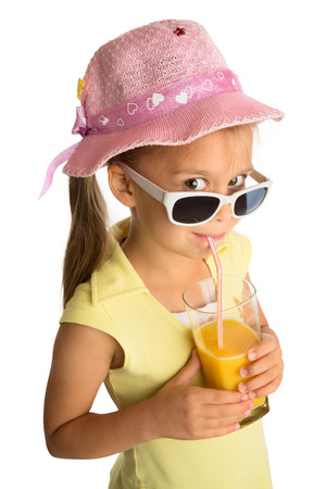 Little girl in pink hat  drinking orange juice through a straw and looking at a viewer over sunglasses