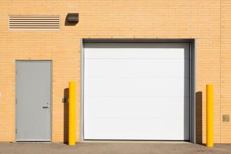 parking facilities: Muelle de carga con una puerta blanca y una puerta gris m�s peque�a Foto de archivo