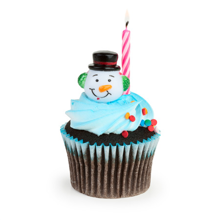 A colorful cupcake with toy snowman on top and burning holiday candle in it, isolated