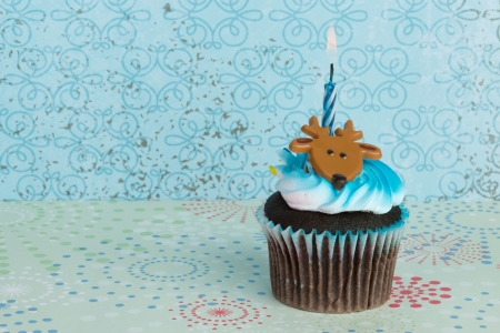 A colorful cupcake with toy deer on top and burning holiday candle inserted, against winter-themed background photo