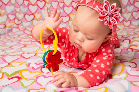 kanzashi: An adorable baby girl wearing a red headband with a decorative flower, playing with toy keys