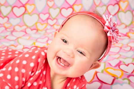 kanzashi: An adorable baby girl wearing a red headband with a decorative flower, lying on a blanked with hearts Stock Photo