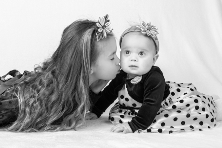 kanzashi: A six years old girl kisses her baby sister in a cheek, while lying on a white surface against white fluffy background  Styled as high contrast black and white