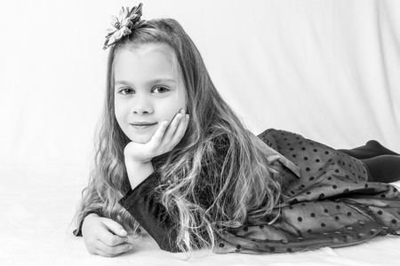 kanzashi: A beautiful six years old girl in a dress and with head decoration, lying on a soft surface against white fluffy background  Styled as high contrast black and white  Stock Photo